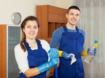 Happy cleaners cleaning living room Royalty Free Stock Photography