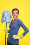 Happy cleaning woman. Cleaning woman happy and satisfied standing with a mop and wearing rubber washing up gloves on a yellow background Stock Photos