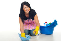 Happy cleaning woman. Kneel and floor wipe with a dust cloth and spray in her house stock images