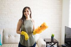 Young housewife cleaning with feather duster. Happy cleaning woman holding orange synthetic feather duster Stock Image