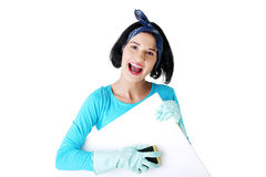 Happy cleaning woman showing blank sign board. Royalty Free Stock Photo