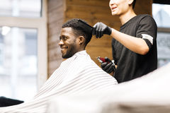 Happy client. Barber taking care of his client hair Royalty Free Stock Photos