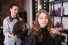 Happy client looking at mirror in salon Stock Image