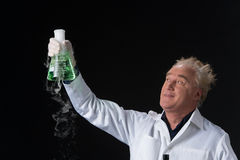 Happy clinician studies in laboratory and holding flask aloft. Stock Photography