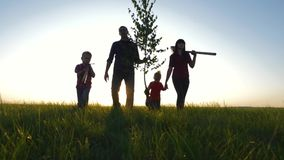 Happy, close-knit family with children, silhouette of farmers outdoors holding hands at sunset. Dad holds a young tree