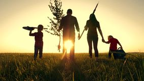 Happy, close-knit family with children, silhouette of farmers outdoors holding hands at sunset. Dad holds a young tree stock footage