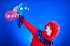 Happy clown with balloon on blue background Royalty Free Stock Images