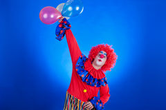 Happy clown with balloon on blue background Stock Photo