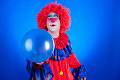 Happy clown with balloon on blue background Stock Photography