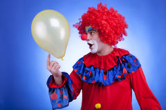 Happy clown with balloon on blue background Stock Image