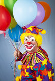 Happy Clown With Balloons. In front of a blue background Stock Images
