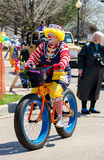 Happy clown on a bike in a small town parade Stock Photography