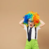 Happy clown boy with large colorful wig. Stock Photos