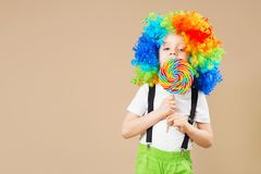 Happy clown boy in large colorful wig. Let`s party! Funny kid cl Royalty Free Stock Photos