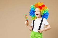 Happy clown boy in large colorful wig. Let`s party! Funny kid cl. Own. 1 April Fool`s day concept. Portrait of a child eating lollipop. Birthday boy Stock Image