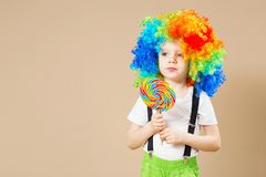 Happy clown boy in large colorful wig. Let`s party! Funny kid cl Royalty Free Stock Photo