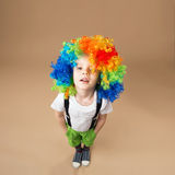 Happy clown boy with large colorful wig Stock Photography
