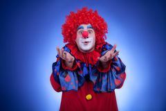 Happy clown in red costume on blue background Royalty Free Stock Image