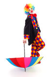 Happy clown with umbrella. Happy clown relies on colorful umbrella Royalty Free Stock Photos