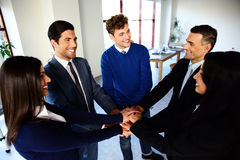 Happy co-workers making pile of hands Stock Image