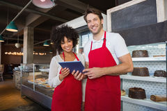 Happy co-workers in red apron holding tablet. At the bakery Stock Image