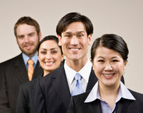 Happy co-workers wearing suits and posing Royalty Free Stock Photos