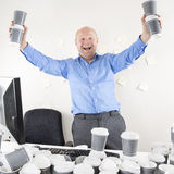 Happy and coffee addicted businessman at office Royalty Free Stock Image