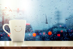 Happy Coffee Mug with smiley face on desk inside glass window, B. Lurred traffic jam light in city as outside view, Relaxing in cafe on rainy day Stock Photography