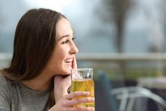 Happy coffee shop customer looking at side. Holding a yellow drink in a terrace royalty free stock images