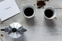 Top view of two coffee cups, italian coffee maker-moka and white card with `Happy` text. Happy coffee time. Top view of two coffee cups, italian coffee maker Royalty Free Stock Photo