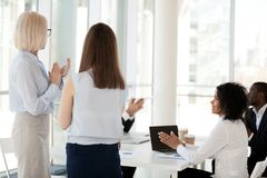 Happy colleagues applaud congratulating coworker with promotion. Back view of businesswoman congratulating female employee with success at briefing, happy stock photos
