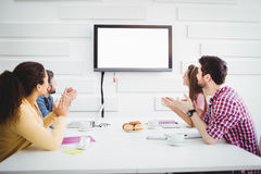 Happy colleagues applauding during meeting at creative office. Happy young colleagues applauding while watching television during meeting at creative office Royalty Free Stock Images