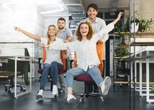 Happy colleagues having fun at workplace, making office chair race. Time for break. Happy colleagues having fun at workplace, making office chair race in royalty free stock photo
