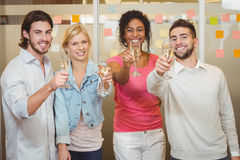 Happy colleagues holding champagne flute in party Stock Images