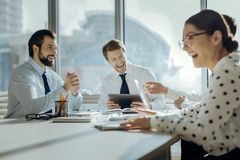 Happy colleagues laughing at funny joke during meeting. Cheerful mood. Upbeat young colleagues sitting at the table in the conference room and laughing at their Royalty Free Stock Photography