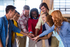 Happy colleagues piling up their hands royalty free stock images