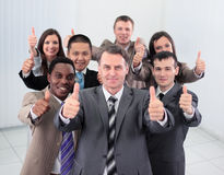 Happy colleagues  showing thumbs up in their office. Stock Image