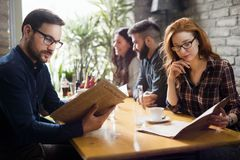 Happy colleagues from work socializing in restaurant. Happy young colleagues from work socializing in restaurant Royalty Free Stock Photo