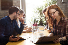 Happy colleagues from work socializing in restaurant. Happy young colleagues from work socializing in restaurant Royalty Free Stock Photography