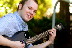 Happy College Boy with Guitar. A happy american college boy playing a guitar looking towards camera. Short hair, shallow depth of field, selective focus Royalty Free Stock Photography
