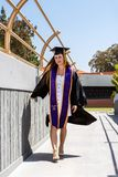 Happy college graduate in tradional attire. Beautiful young female student walking with attitude and confidence while dragging hand along student walkway of royalty free stock photos