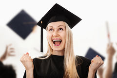 Happy college graduate wearing cap and gown Stock Photos