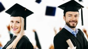 Happy college graduates wearing gowns at graduation ceremony stock footage
