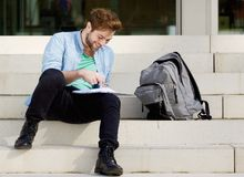 Happy college student sitting outside on campus. Portrait of a happy college student sitting outside on campus reading through notes Stock Photos