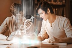Happy college students analysing dna on digital interface Stock Photos