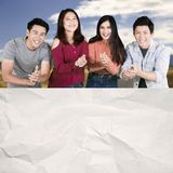 Happy college students applaud near a blank paper. Group of happy college students applauding at the camera while showing blank crumpled paper stock images