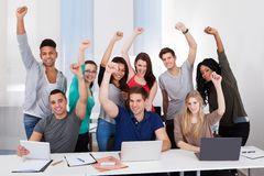 Happy college students celebrating success in classroom Stock Photo