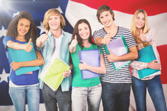 Composite image of happy college students gesturing thumbs up. Happy college students gesturing thumbs up against close-up of flag Royalty Free Stock Photography