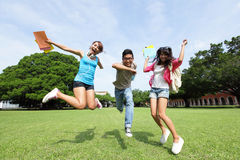 Happy College students. Jump and smile to you on campus lawn, asian Royalty Free Stock Images