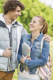 Happy college students looking at each other at campus Stock Photos